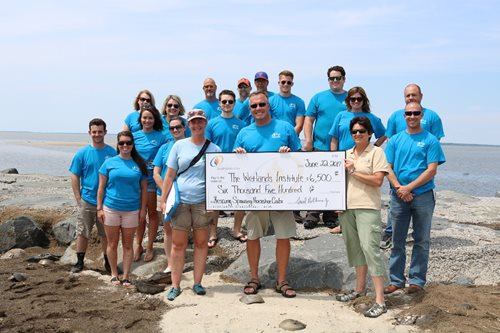 volunteers with a check from SJG for the Wetlands Institute