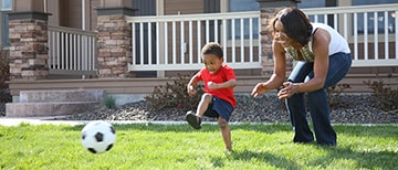 a mother and son playing soccer in their yard